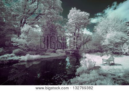 Stunning infra red landscape image of old bridge over river in countryside