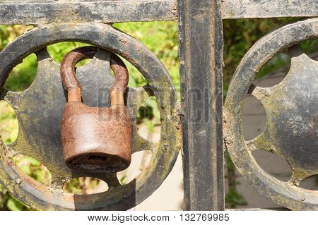 Old rusty lock on a metal gate into the garden. Lock on the iron gate. Symbol imprisonment and slavery. Property security chain. Closed iron gate with a lock. Safe lock.