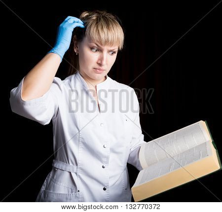 Doctor in gown and rubber gloves reading a medical book to confirm that his patient is in excellent health.