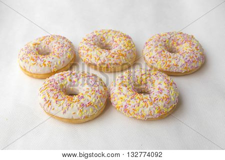 Mound of doughnuts. Crumpet for tea. Tasty food cakes. Delicious classic cakes: fried doughnuts glazed with caramel. Nutritious dish that promotes obesity.