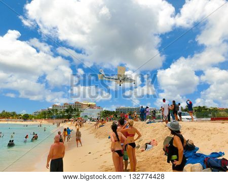 Philipsburg, Sint Maarten, Netherlands - May 14, 2016: The beach at Maho Bay is one of the world's premier planespotting destinations. Airplanes landing at the Princess Juliana Airport fly over beachgoers.