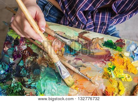 Brush And Oil Paints On A Palette, Paint A Picture Of The Artist's Hands, Texture Mix Paint In Diffe