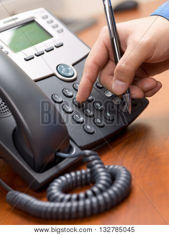 Cropped Image Of A Person Dialing Number On Landline Phone