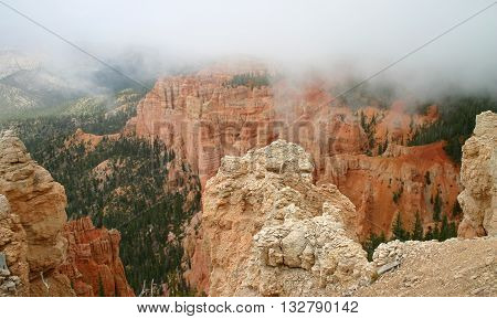 low clouds advance over red sandstone cliffs in Utah