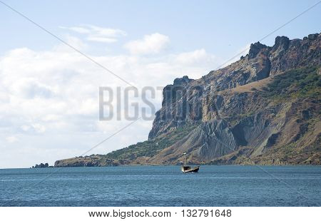 Europe Russia Crimea. Small boat at sea off the cliff in about Koktebel.