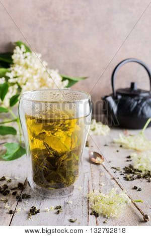 Healthy medicine green tea with elder flower in glass on old white wooden tafel with elder flower branches. Copy space.
