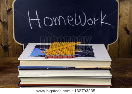 stack of books and pencils on wood background in front of chalkboard written homework