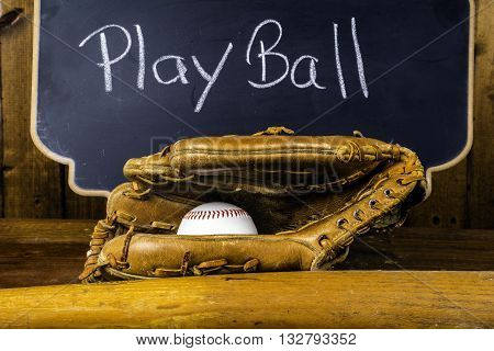 baseball bat glove and ball on wood background in front of chalkboard written play ball