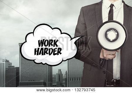 Work harder text on speech bubble with businessman and megaphone on city background