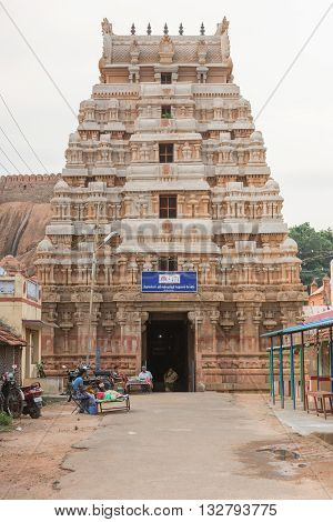 Chettinad India - October 16 2013: The gopuram of the Lord Vishnu temple in Thirumayam village. The battlements of the fort in background. A few people at entrance.