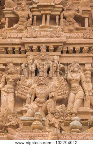 Chettinad India - October 16 2013: Detail of Shiva temple gopuram in Thirumayam. Multi-armed God surrounded by women.