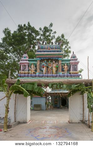Chettinad India - October 17 2013: Entrance to the shrine of Shani known as Satan in the West in Kadiapatti. Image features wedding of Shiva and Parvati. The blue skinned person is Lord Vishnu. He gives his sister the green-skinned female in the middle