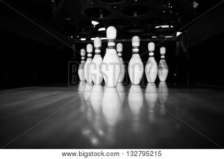 Ten White Pins In A Bowling Alley Lane