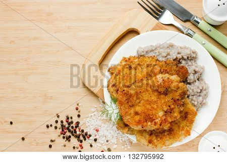 Meat pork chop in bread crumbs garnished with green buckwheat hearty and healthy lunch dish top view blank space for text
