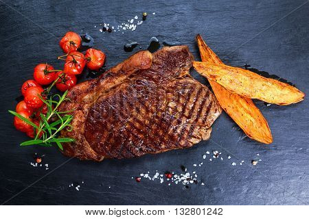 Grilled Beef Sirloin Steak on blue stone background, with vegetables