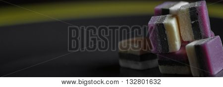 Licorice candy on black plate and yellow background