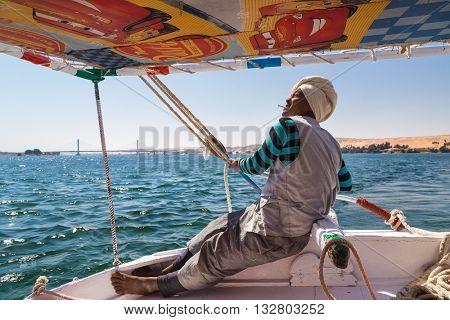 NILE, EGYPT -  FEBRUARY 8, 2016: Nubian felucca sailing crew member holding ropes on trip on the Nile.