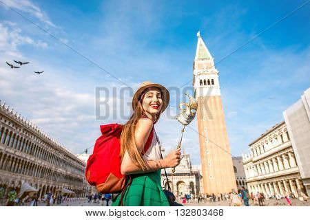 Young female traveler having fun with carnaval mask standing on San Marco square in Venice.