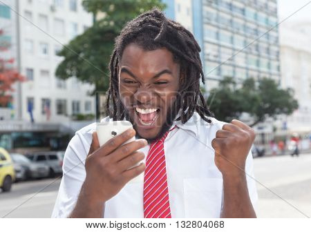 Cheering african american businessman with dreadlocks and phone outdoor in the city