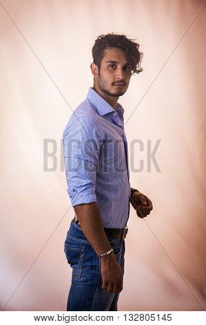 Portrait of brunette young man in light blue shirt and jeans, standing in studio shot against light background