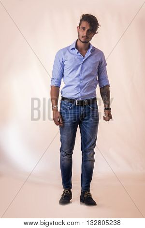 Portrait of brunette young man in light blue shirt and jeans, standing in studio shot against light background. Full length photo