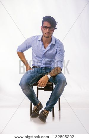 Portrait of brunette young man in light blue shirt and jeans, sitting in studio shot against light background. Full length photo