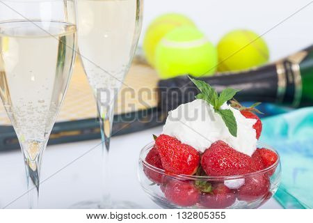 Strawberries with whipped cream and mint leaves and glasses with champagne