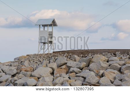 Lifeguard station over rocky road with blue sky background