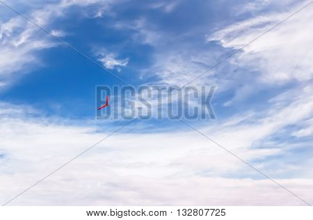 Red boomerang flies in the blue sky among pure white clouds.