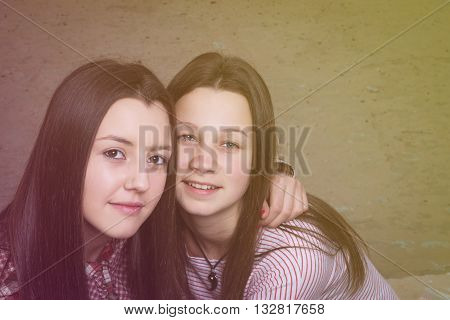two young girls were photographed by a close up in an embrace