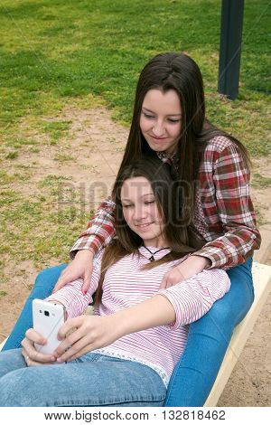 two girls were photographed in park taking a selfie