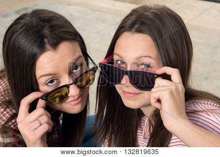 two young girls were photographed in park in sunglasse