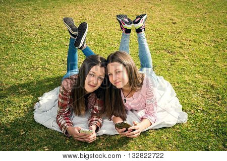 two young beautiful girls write in mobile phones lying in park
