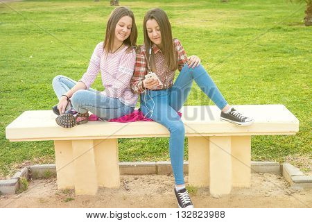 two girls were photographed on a shop looking together in the mobile phone