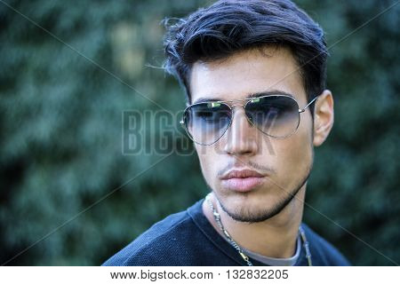 Headshot of handsome young man in city street, looking to a side, wearing sunglasses