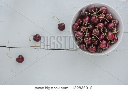 Cherries in a white bowl, stand on a blue wooden table as a thing, view from above