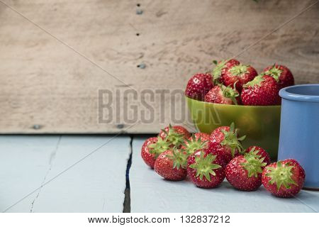 Scattered strawberry fruits in green bowl and with juice in blue clay cup on blue wooden table with wooden wall in background