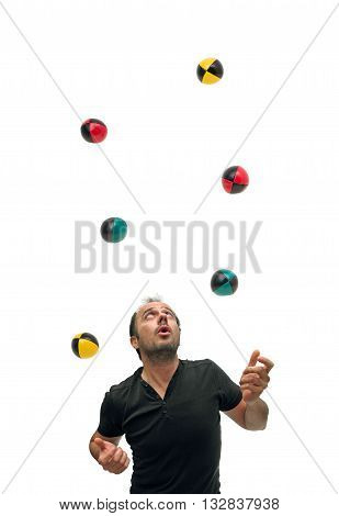 Caucasian man juggling with six colourful balls