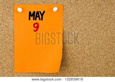 9 May Written On Orange Paper Note