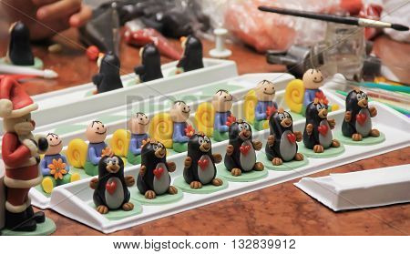 figures of marzipan modeling preparation of sweet decorations for cakes and pies women's hands marzipan museum soft focus