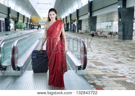 Pretty Indian woman wearing saree clothes and walks in the airport terminal while carrying a suitcase