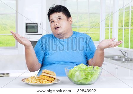Picutre of overweight man thinking to choose salad or burger shot in the kitchen at home