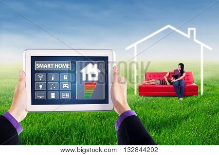 Image of smart house controller applications on the digital tablet screen with young woman and her child sitting on sofa under a house symbol