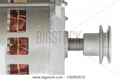 Fragment of alternating current motor with pulley and ventilation holes in the housing through which can be seen winding closeup on a light background