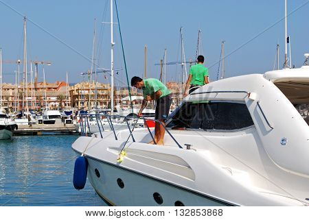 PUERTO SOTOGRANDE, SPAIN - JULY 18, 2008 - Men cleaning a yacht in the marina Puerto Sotogrande Cadiz Province Andalucia Spain Western Europe, July 18, 2008.