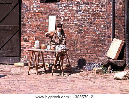 COALPORT, UK - APRIL 28, 1991 - Potter at work in the yard at the Coalport China Museum Coalport Shropshire England UK Western Europe, April 28, 1991.