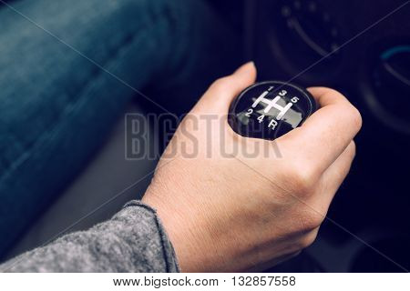 Female driver hand shifting gear manually selective focus