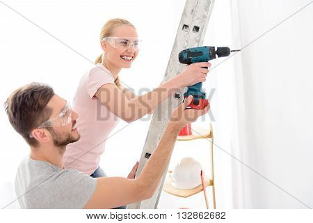 Together always much easier. Young smiling man helping girl standing on stepladder, keeping drill and making hole in white wall