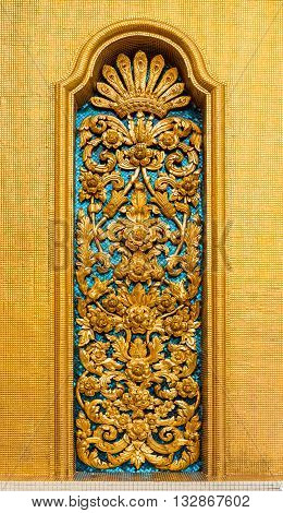 golden floral sculpture of traditional Thai style on temple wall