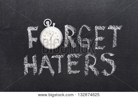 forget haters phrase handwritten on chalkboard with vintage precise stopwatch used instead of O
